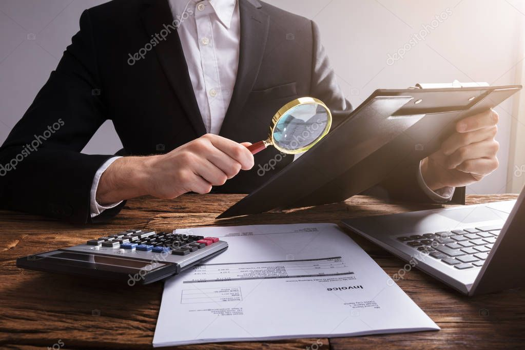 Businessperson Analyzing Document On Clipboard With Magnifying Glass Over Wooden Desk At Workplace