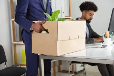 Mid Section View Of A Businessperson Packing Belongings In Cardboard Box At Workplace