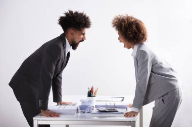 Side View Of Two Young Businesspeople Shouting At Each Other At Workplace