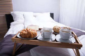 Fotografie Čerstvé croissanty a šálek čaje na posteli, u snídaně