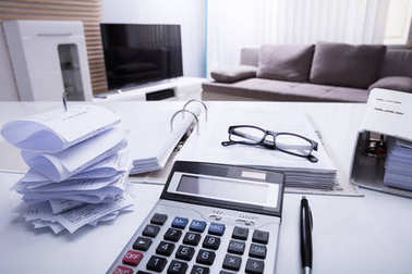 Close-up Of Folders With Receipts And Calculator On White Desk In Bedroom