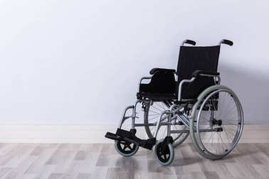 Black Colored Empty Wheelchair In Front Of Wall