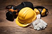 Fotografie Close-up Of Yellow Hard Hat With Safety Equipment On Wooden Background