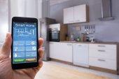 Detail osoby ruky pomocí systému Smart Home na mobilní telefon v kuchyni