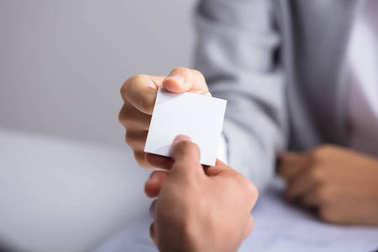Close-up Of Businessperson's Hand Giving Blank White Card To Partner