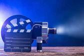 Fotografie Detail z osvětlené filmová kamera s role fólie a desky klapky na dřevěný stůl