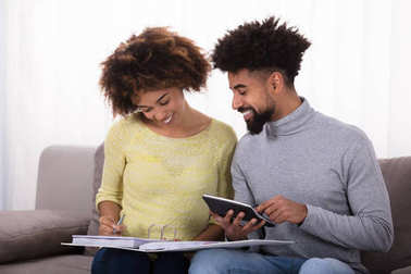Young Couple Sitting On Sofa Calculating Bill With Calculator