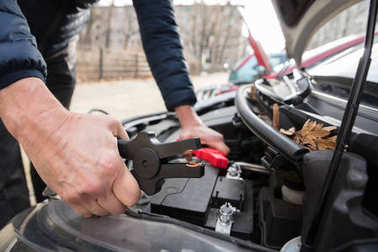 Close-up Of A Person's Hand Using Jumper Cables To Charge Car's Dead Battery