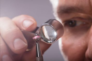 Close-up Of A Person's Hand Checking Diamond Through Magnifying Loupe