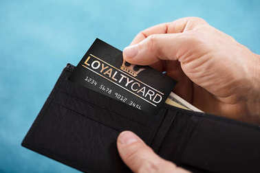 Close-up Of A Person's Hand Removing Black Loyalty Card From Wallet