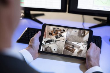 Close-up Of A Businessman Looking At CCTV Camera Footage On Digital Tablet