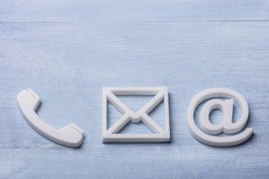 High Angle View Of White Phone, Email and Post Icons Isolated On Wooden Plank