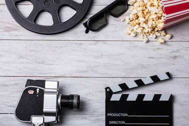 Elevated View Of Spilled Popcorn With Clapperboard, 3d Glasses, Film Reel And Movie Camera
