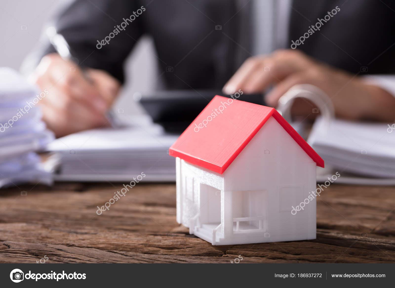 Gros plan modèle maison avec toit rouge sur bureau bois