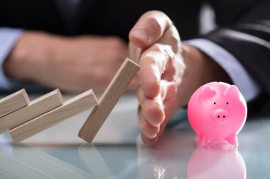 Close-up Of A Businessman's Hand Stopping Wooden Blocks From Falling On Piggybank Over Desk