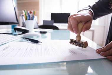 Close-up Of A Businessperson's Hand Stamping Approved On Contract Paper In Office