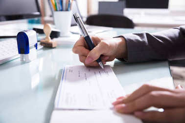 Close-up Of A Businessperson's Hand Signing Cheque With Pen In Office