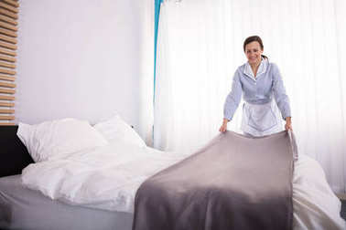 Smiling Female Housekeeper Making Bed In Hotel Room