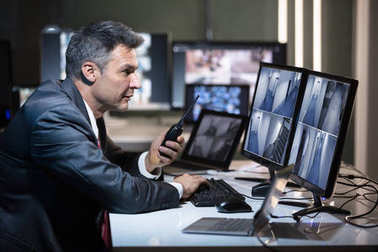 Businessman Talking On Walkie Talkie While Looking At CCTV Camera Footage On Multiple Computer Screen