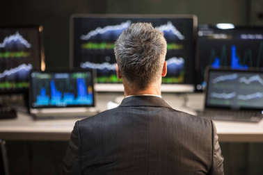 Male Stock Market Broker Looking At Computer And Laptop Showing Graph On Screen