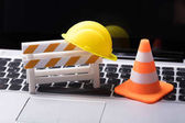 Photo Road Barrier With Hard Hat And Traffic Cone On Laptop Keypad