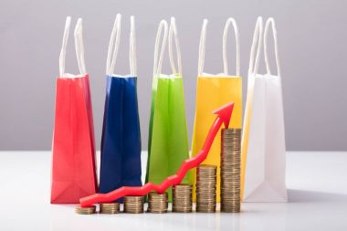 Close-up Of Stacked Coins With Red Arrow In Front Of Multi Colored Shopping Bags