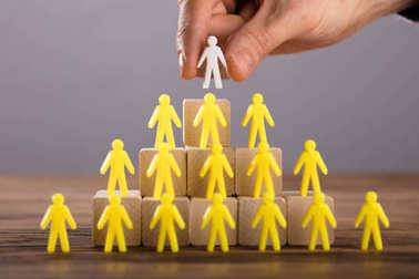 Close-up Of A Person Placing White Human Figure Standing On Top Of Yellow Human Figures