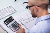 Podnikatel, pomocí kalkulačky pro výpočet faktury na stůl
