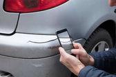 Fotografie Detail osoby ruky s fotografii poškozeného vozu prostřednictvím Smartphone