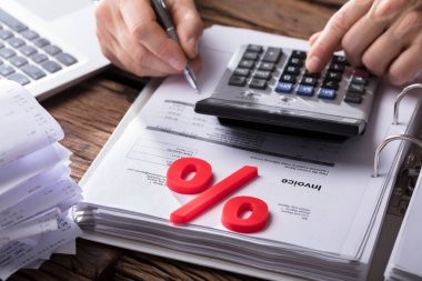 Close-up Of Red Percentage Symbol With Businessperson Calculating Bill