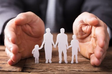 Close-up Of A Businessperson's Hand Protecting Family Figures On Wooden Desk