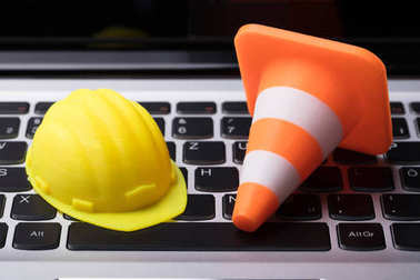 Close-up Of Hard Hat And Traffic Cone On Laptop Keypad