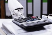 Close-up Of A Robotic Hand Using Calculator