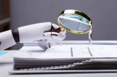 Fotografie Close-up Of A Robotic Hand Holding Magnifying Glass Over Invoice At Workplace