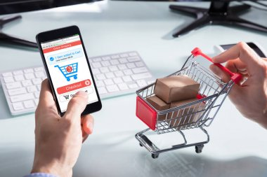 A Person's Hand Holding Cart With Cardboard Boxes While Shopping Online On Mobile Phone