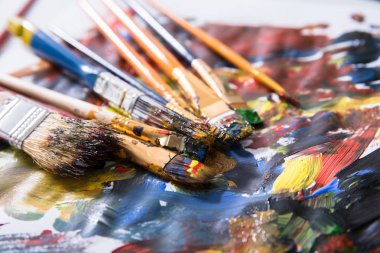 Close-up Of Various Messy Paintbrushes With Multi Colored Paint On Canvas Paper