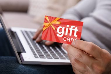 Close-up Of A Person's Hand Working On Laptop Holding Gift Card