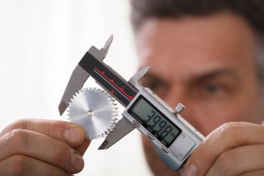 Close-up Of A Man's Hand Measuring Gear's Size With Digital Electronic Vernier Caliper