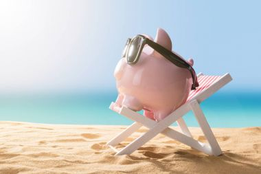 Close-up Of A Pink Piggy Bank Wearing Sunglasses Relaxing On Deck Chair