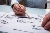 Human Hand Drawing Sketch Of A Car With Pencil On Paper