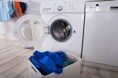 Prázdnou pračku s hromadou špinavé prádlo do koše v prádelně