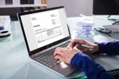 Close-up Of A Businesspersons Hand Analyzing Invoice On Laptop At Workplace