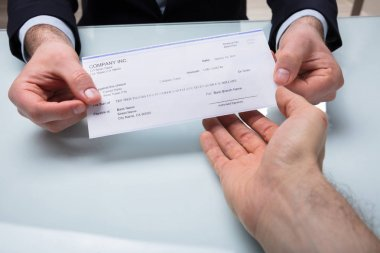 Close-up Of A Businessman's Hand Giving Cheque To His Colleague At Workplace