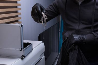 Close-up Of A Robber's Hand Wearing Gloves Stealing Jewelry From Box