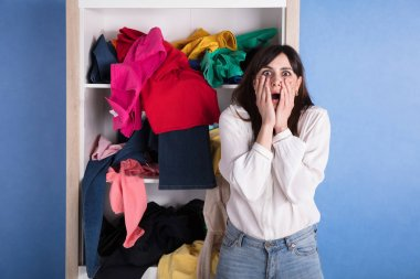 Portrait Of A Shocked Woman In Front Of Scattered Clothes On Shelf