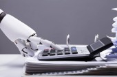 Close-up Of A Robotic Hand Calculating Bills Using Calculator In Office