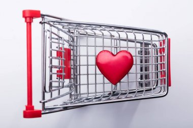 High Angle View Of Shopping Cart With Red Heart On White Background