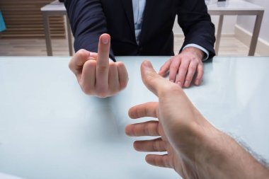 Close-up Of Businessman's Hand Showing Middle Finger To His Partner In Office