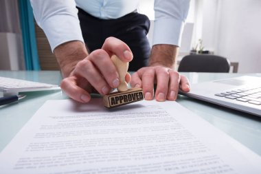 Close-up Of A Businessman's Hand Stamping Approved On Document In Office