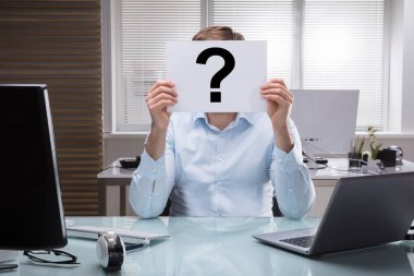 Businessperson Holding Placard With Question Mark Sign In Front Of Face In Office
